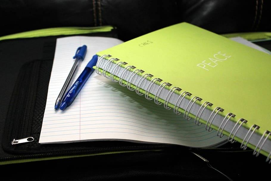 A green notebook, paper and pencils