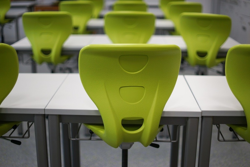 green chairs and white desks in the empty test room