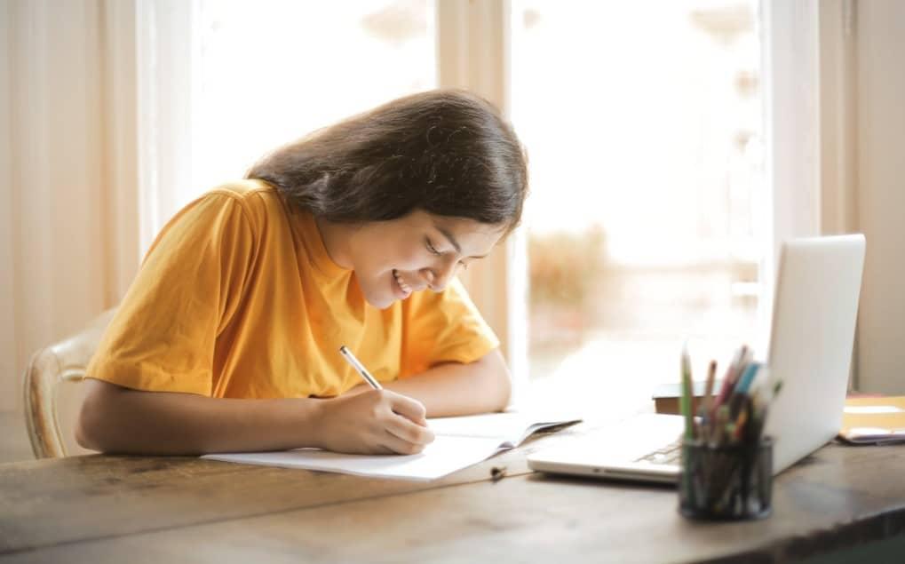 girl writing happily