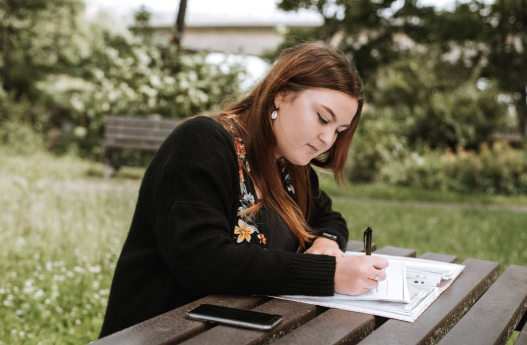girl sitting on a bench and writing